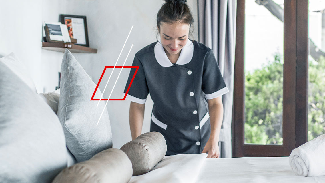 Housekeeper turning a bed in a hotel room