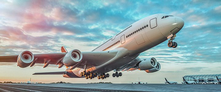 Large airplane taking off from the runway at an airport at sunset