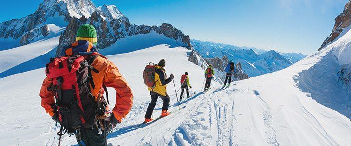 Travelers following a ski hiking trail on mountain tour